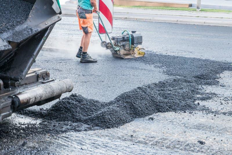 路工作者变紧密与一台振动的拨弹机的沥青在路,德国 图库摄影