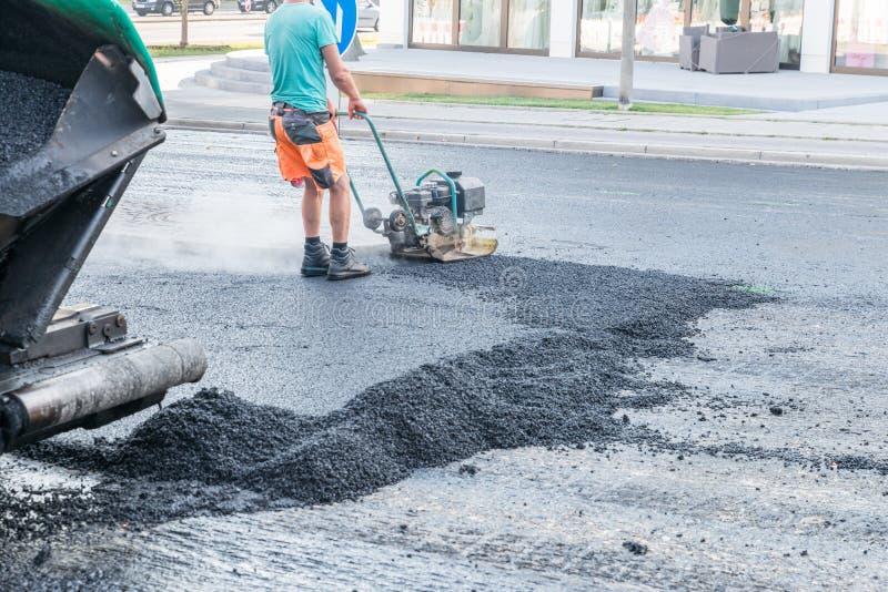 路工作者变紧密与一台振动的拨弹机的沥青在路,德国 库存照片