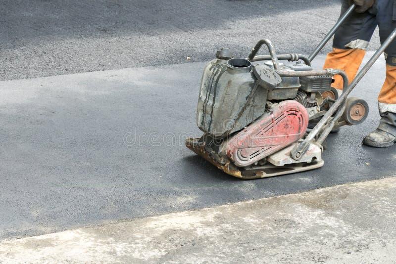 路工作者变紧密与一台振动的拨弹机的沥青在路 有压紧机的工作者在路工地工作 免版税库存图片