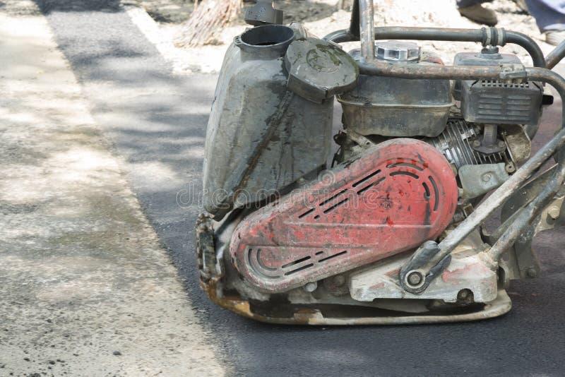 路工作者变紧密与一台振动的拨弹机的沥青在路 有压紧机的工作者在路工地工作 库存图片