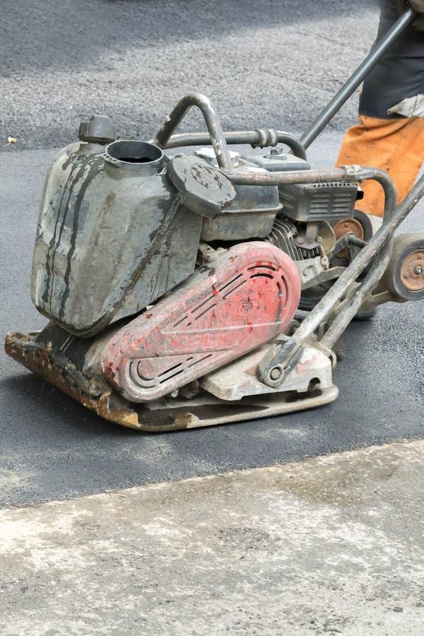 路工作者变紧密与一台振动的拨弹机的沥青在路 有压紧机的工作者在路工地工作 ?? 库存图片