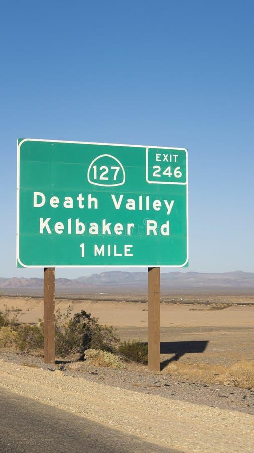 路显示死亡谷的距离标志出口在莫哈韦沙漠,跨境的到拉斯维加斯,加利福尼亚,美国 库存图片