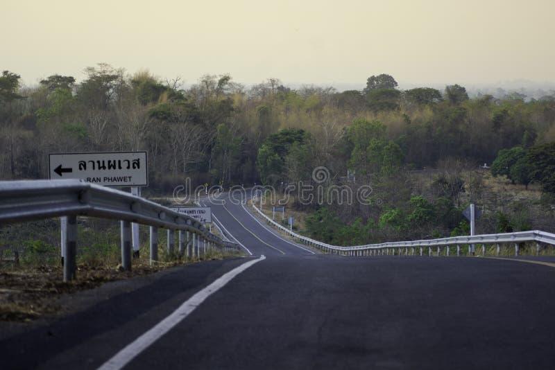 路有一线黄线,并且有在陡峭的左边的一个警报信号下来从他 免版税库存图片