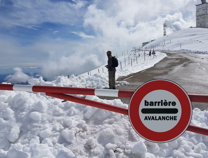 路标中止 警告在山的危险 雪崩撤退 在积雪覆盖的山的危险在云彩中冠上 库存图片