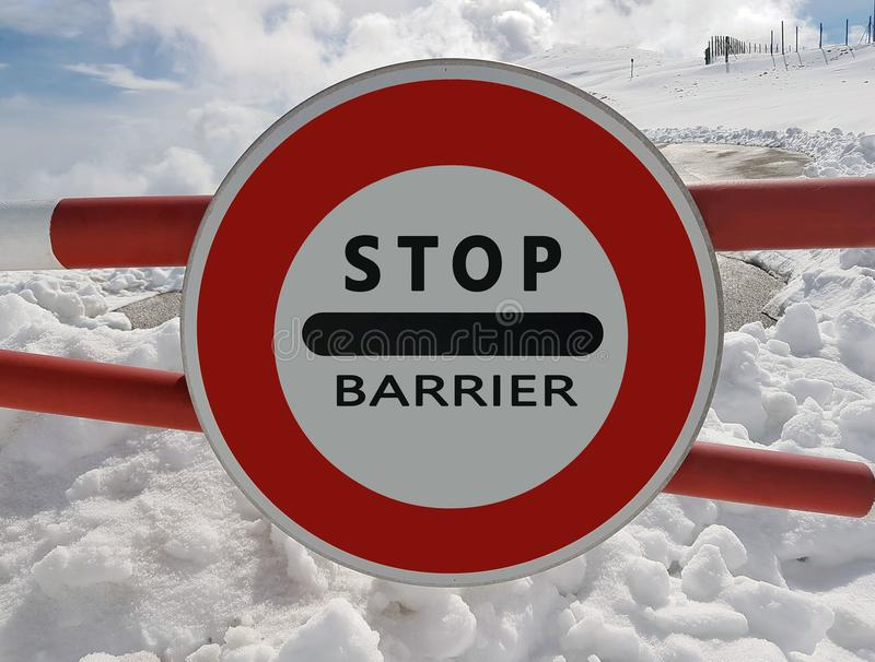 路标中止 警告在山的危险 雪崩撤退 在积雪覆盖的山的危险在云彩中冠上 T 库存图片