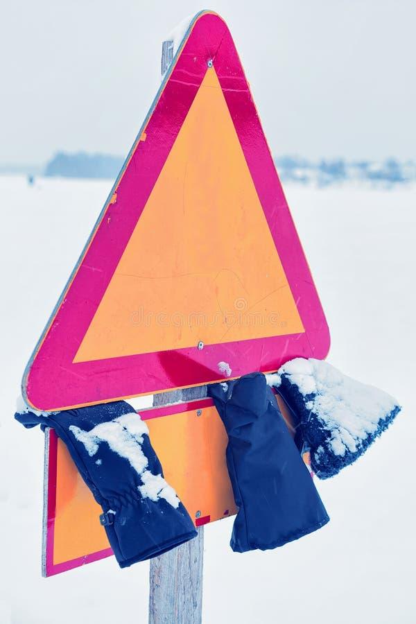 路标和失去的手套在街道在冬天罗瓦涅米 免版税库存图片
