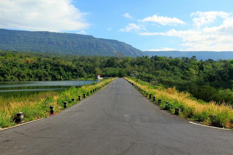 路沿一个美丽的河或湖舒展,有山、蓝天、白色云彩和绿色森林的前景的 免版税库存照片
