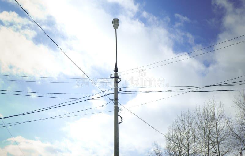 路灯柱在输电线的交叉点在蓝天背景的与白色云彩 免版税库存照片