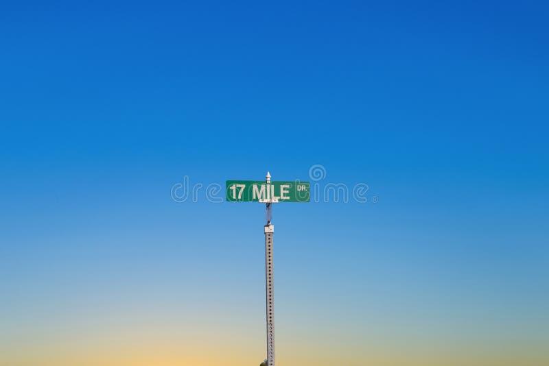 路牌在圆石滩的17英里驱动在日落光的蒙特里附近 免版税图库摄影