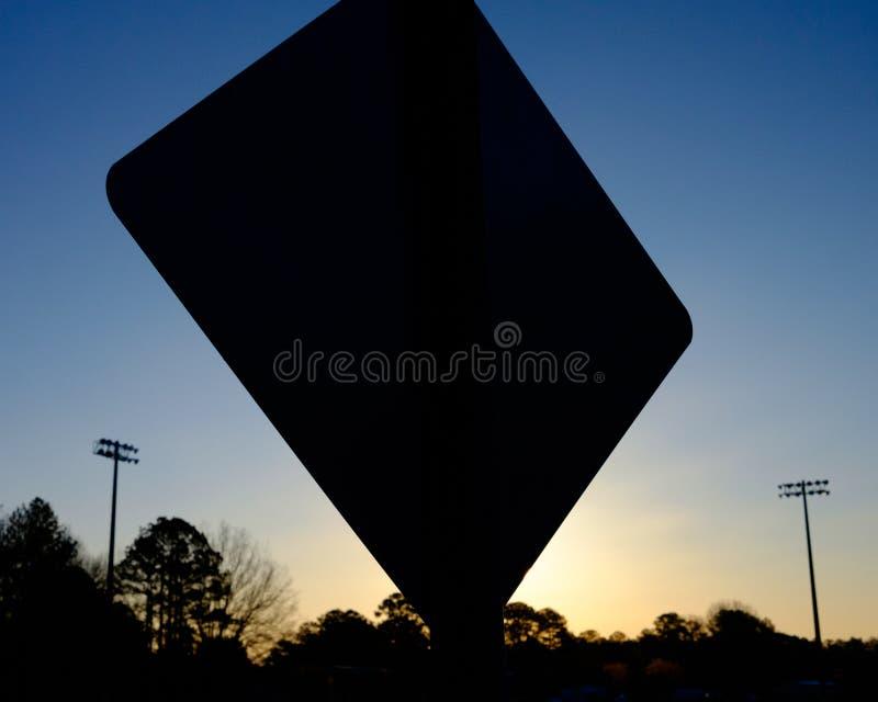 路牌的剪影在黎明 免版税库存图片