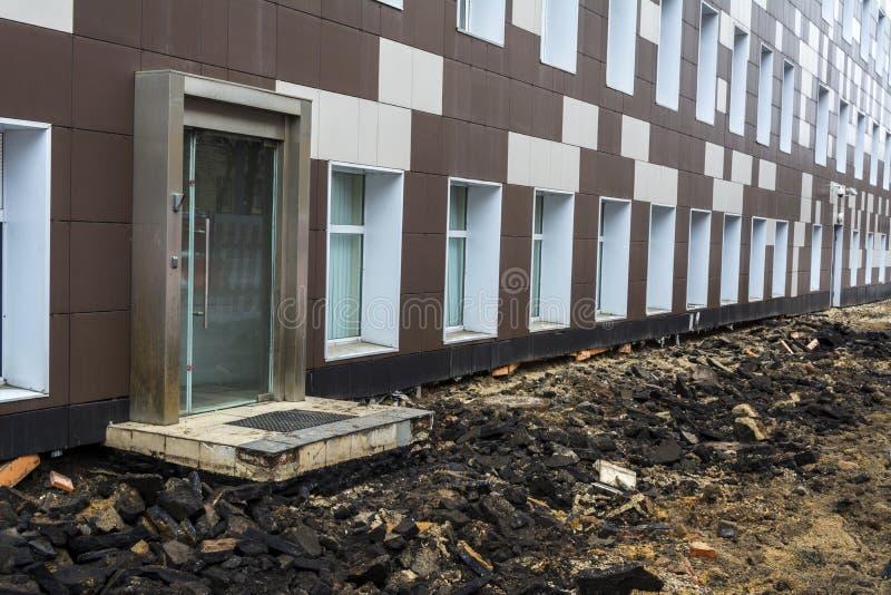 路的修理在办公楼对面的 完全地取消了沥青 库存图片