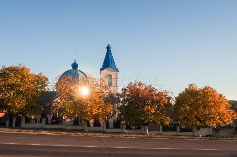 路的基督教会在日落的秋天 免版税库存图片
