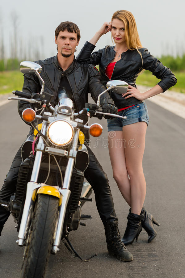 路的美丽的夫妇骑自行车的人摩托车骑士 库存照片
