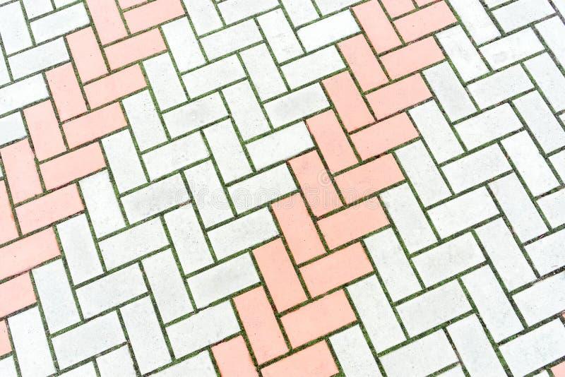 路的马赛克铺面 纹理与草的砖地板在空白 免版税图库摄影