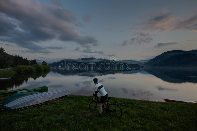 路看对有云彩和反射的美丽的湖的自行车司机 免版税库存照片