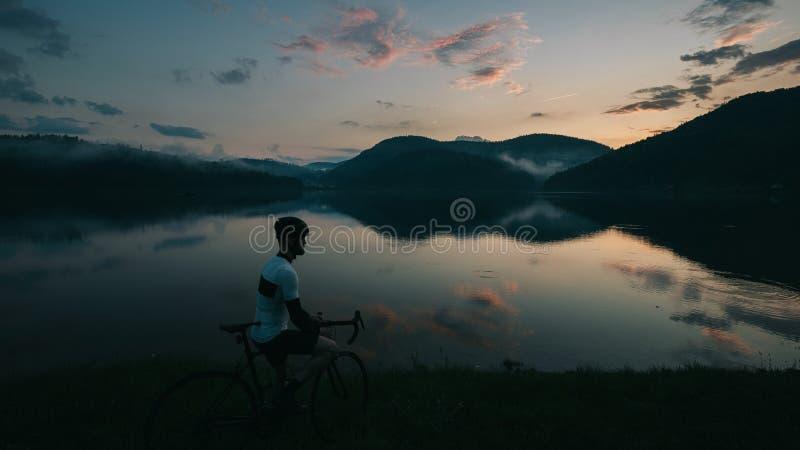 路看对有云彩和反射的美丽的湖的自行车司机 免版税图库摄影