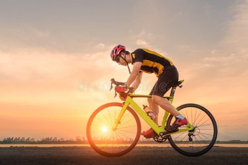 路自行车骑自行车者人循环 骑自行车炫耀健身运动员在一条开放路的骑马自行车对日落 图库摄影