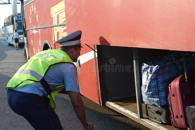 路警察巡逻的审查员检查城市间的乘客公共汽车的行李舱 免版税库存图片