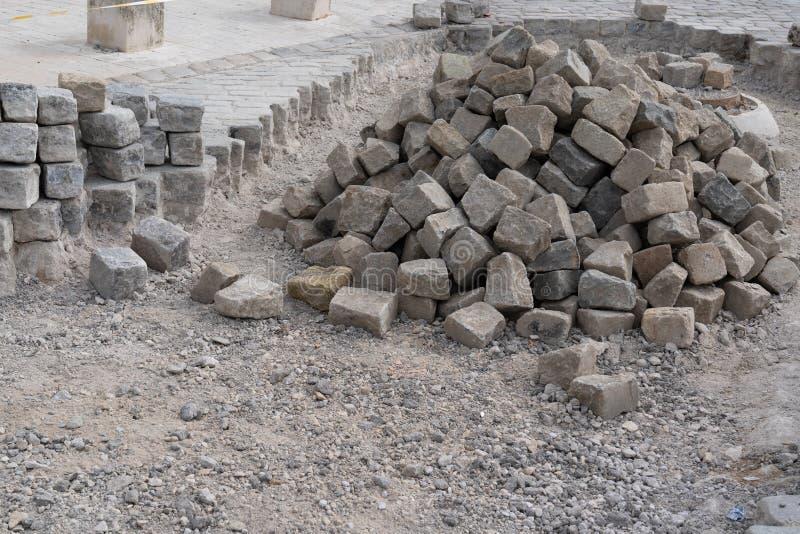 路面花岗岩鹅卵石的建筑石瓦片在街道工作 免版税库存图片