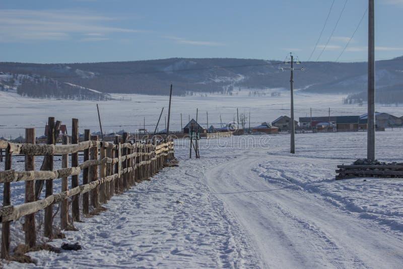 路风景在雪的与木篱芭在Khovsgol的村庄 库存图片