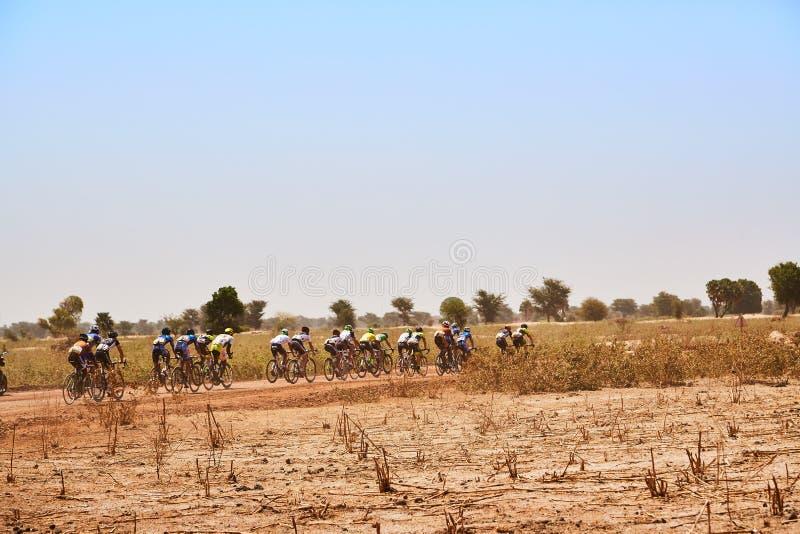 路骑自行车的人在沙漠编组赛跑在农村路 免版税库存图片