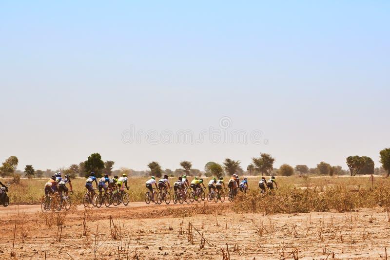 路骑自行车的人在沙漠编组赛跑在农村路 库存图片