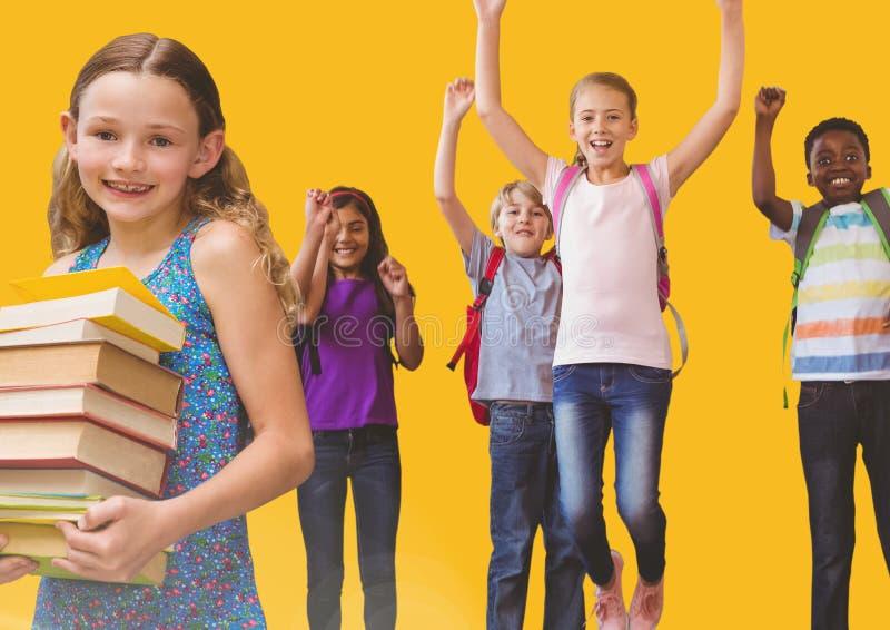 跳为喜悦的孩子在有书和黄色背景的屋子里 免版税库存图片
