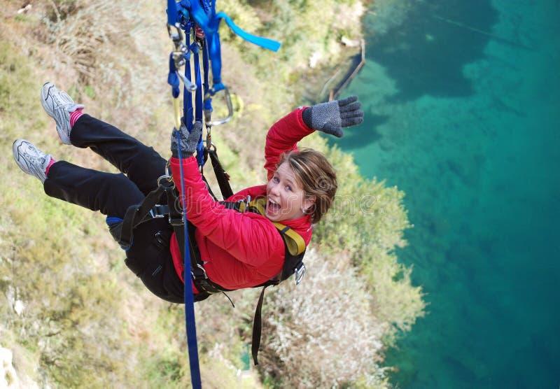 跳从高在湖橡皮筋样式的峭壁 免版税库存图片