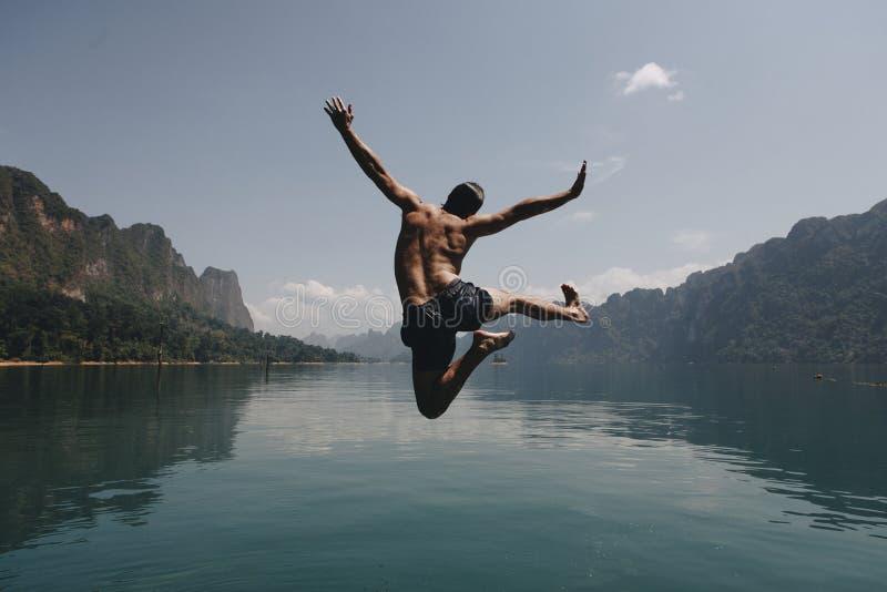 跳充满喜悦的人由湖 免版税库存照片