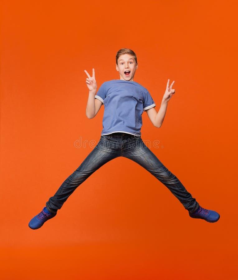 跳和显示在桔子的男孩和平姿态 库存照片
