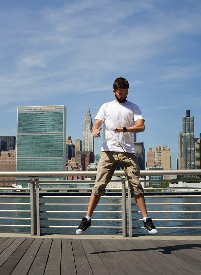 跳和看他的手表的人在纽约 库存照片