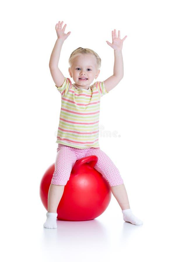 跳在一个大球的微笑的儿童女孩隔绝了白色背景 免版税库存照片