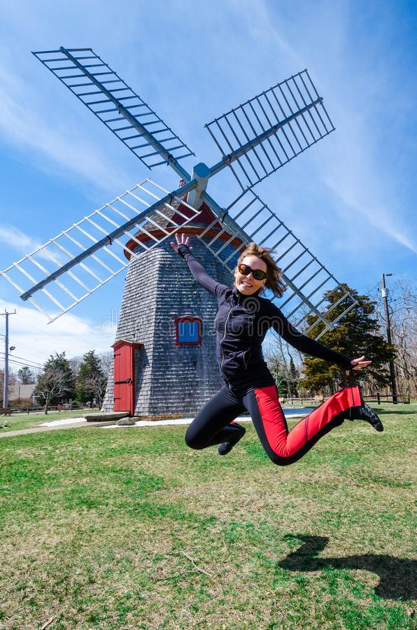 跳在伊斯特汉风车前面的妇女 历史的古板的磨房在一个鳕鱼角公园坐在马萨诸塞 Fisheye 免版税库存图片