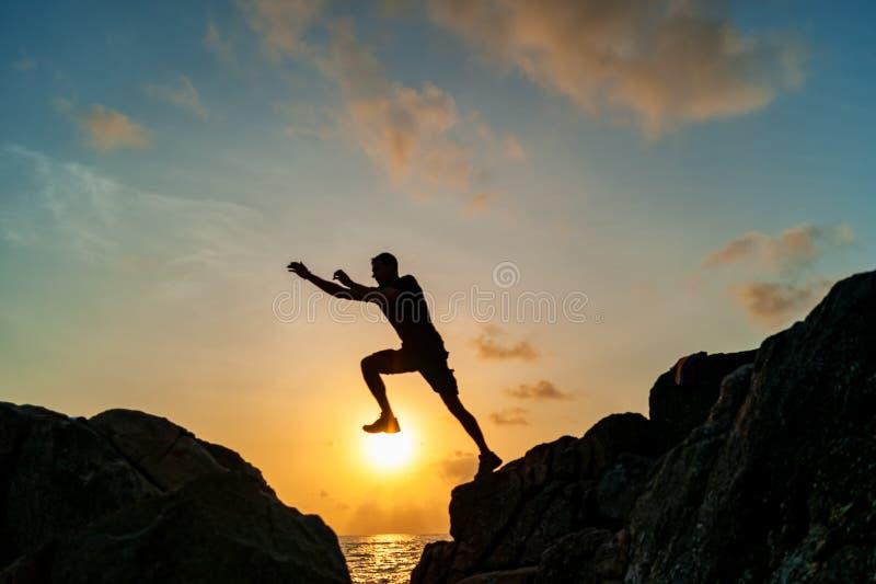 跳在岩石的人在日出 免版税库存图片