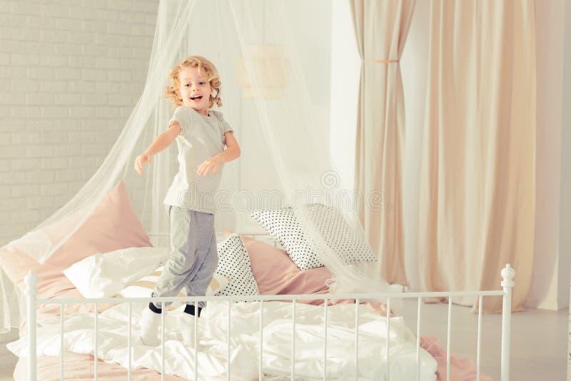 跳在床上的男孩 免版税库存图片