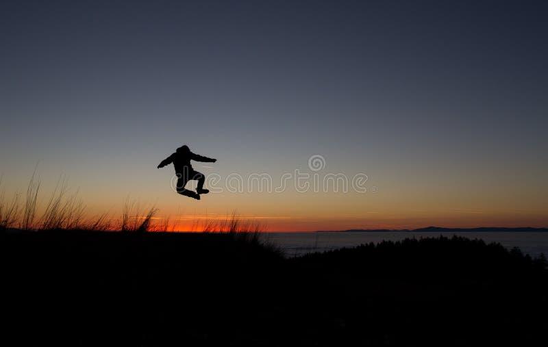 跳在日落的现出轮廓人 免版税库存图片