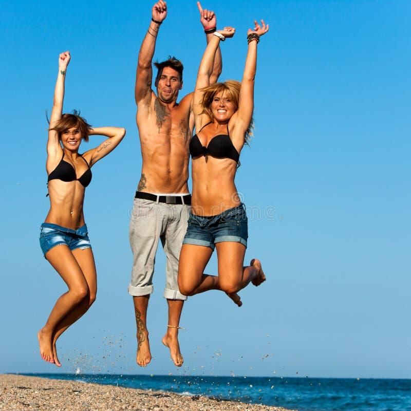 跳在海滩的组新朋友。 免版税库存照片