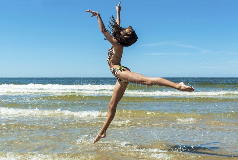 跳在海滩的美女 免版税库存照片