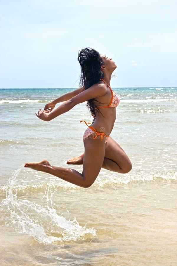 跳在海的妇女 免版税库存图片