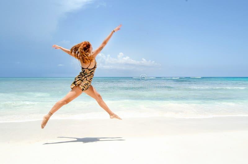 跳在海滩的女孩 免版税图库摄影