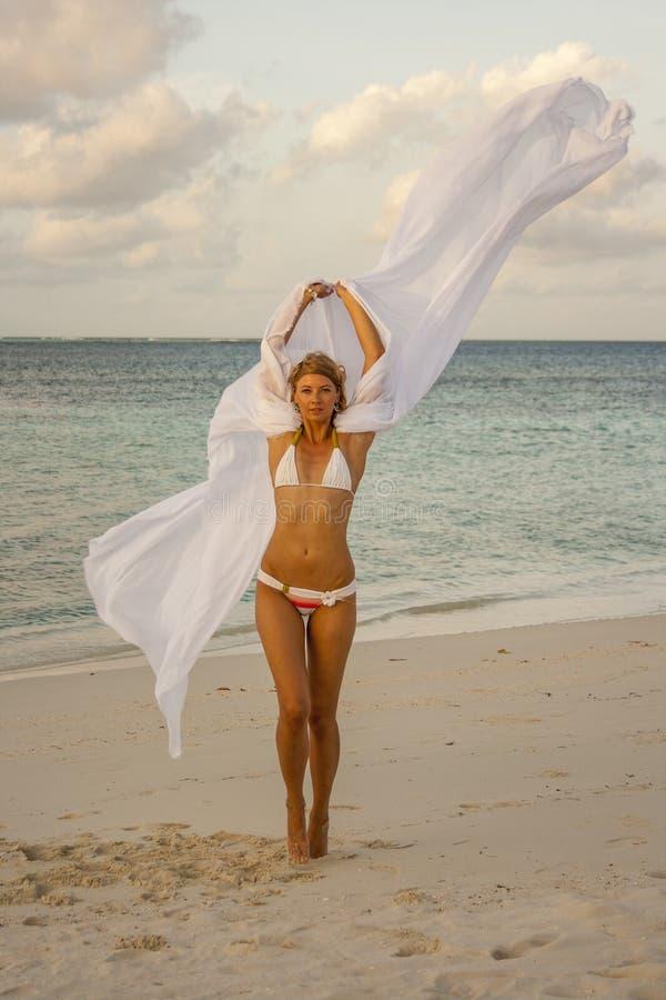 跳在海滩的妇女 库存图片