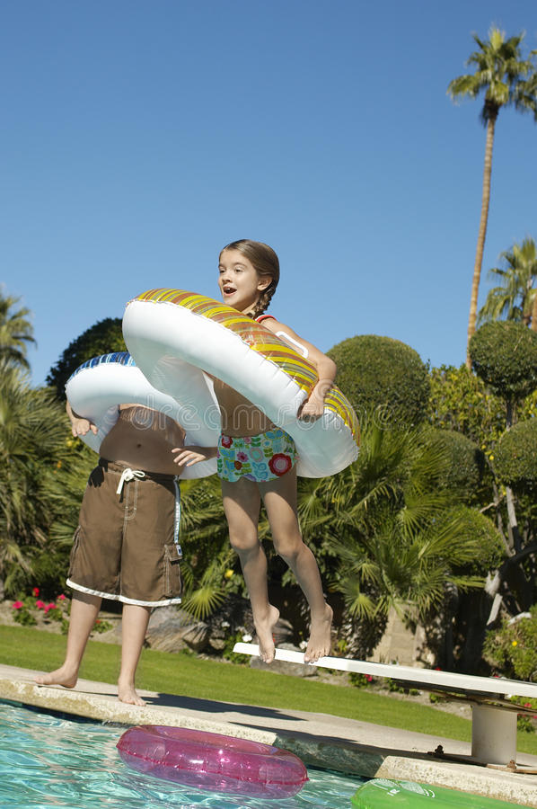 跳在游泳池的女孩 免版税库存图片
