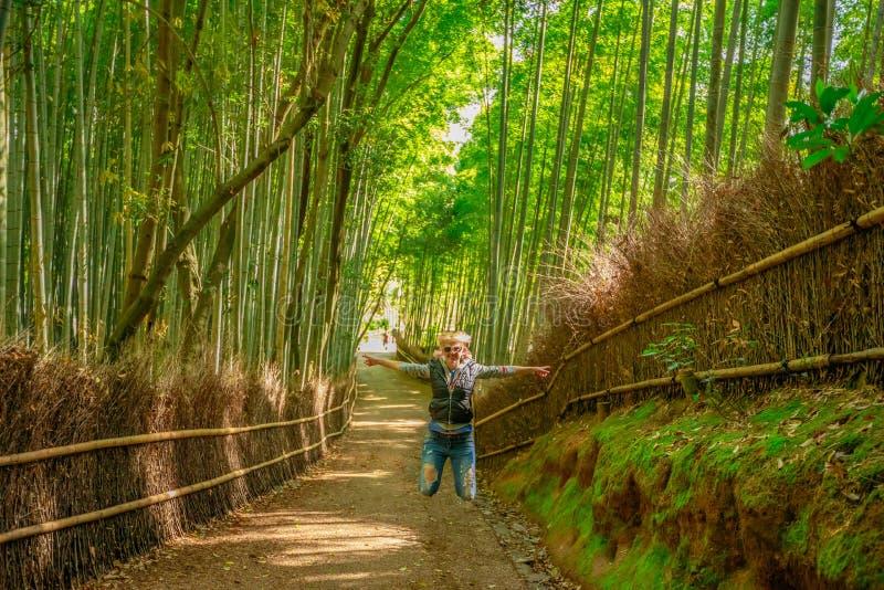 跳在竹森林里的妇女 免版税库存照片