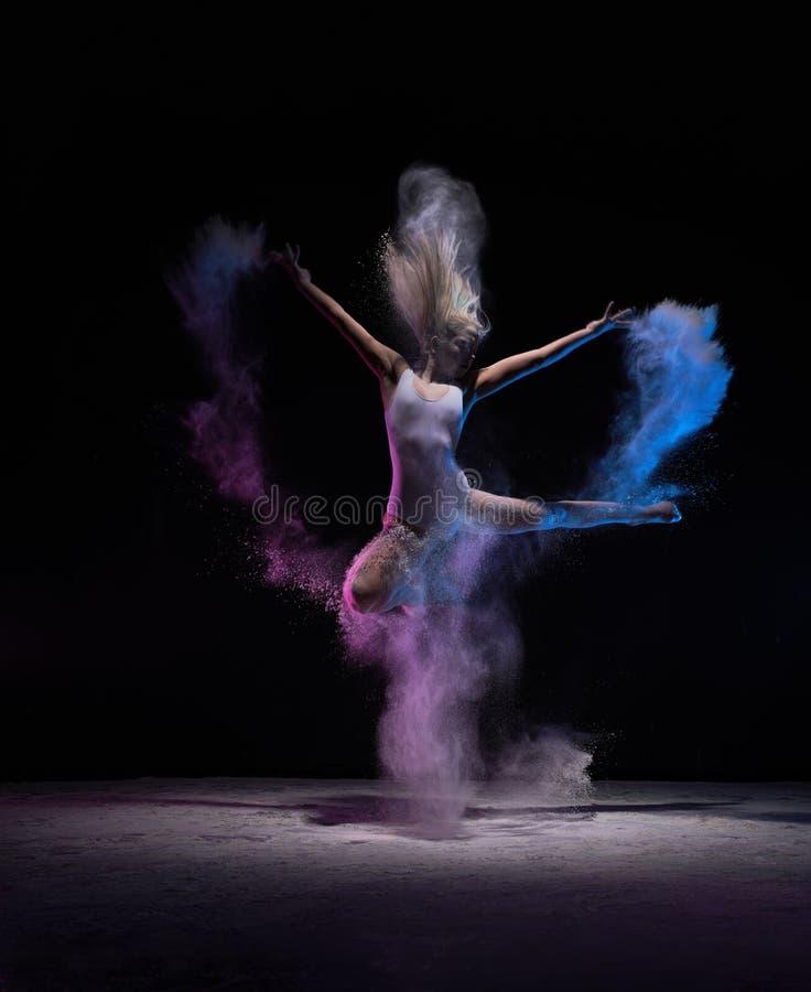 跳在粉末云彩的舞蹈家,在行动 免版税图库摄影