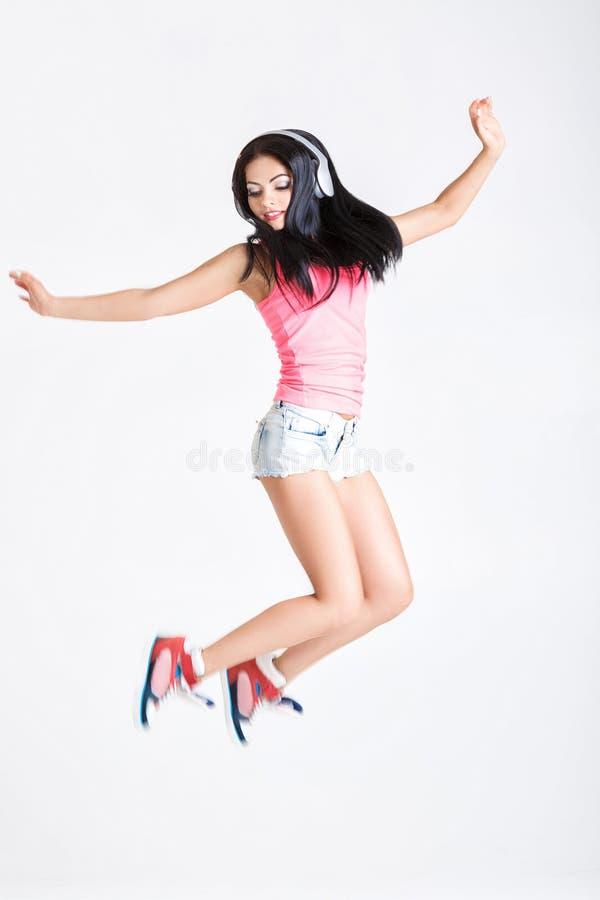 跳在耳机的妇女到音乐 免版税库存照片