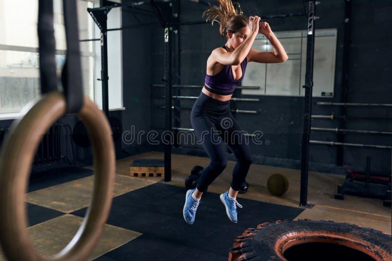 跳在CrossFit健身房的巨大的轮胎的妇女 免版税库存照片