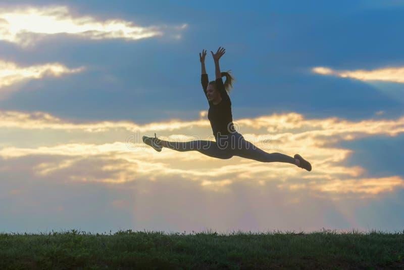 跳室外早晨云彩背景,运动员妇女的运动的年轻女人跳美好的日出早晨锻炼 库存照片