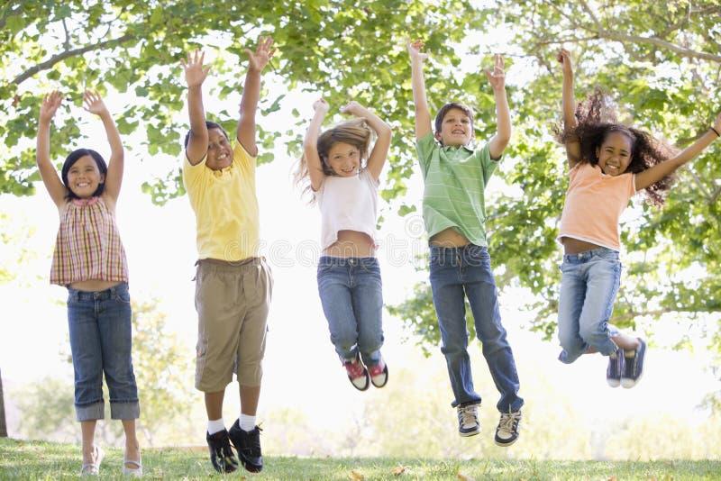 跳户外微笑的年轻人的五个朋友 免版税图库摄影