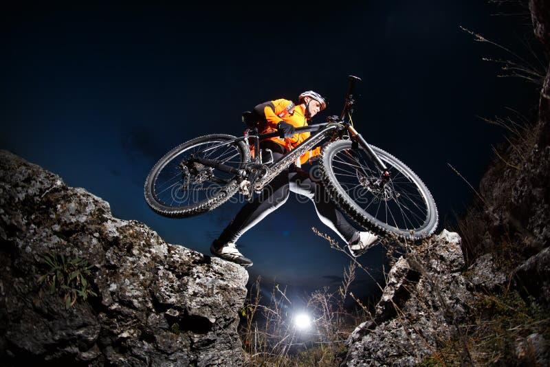 跳横跨与他的自行车的岩石的运动员 免版税图库摄影