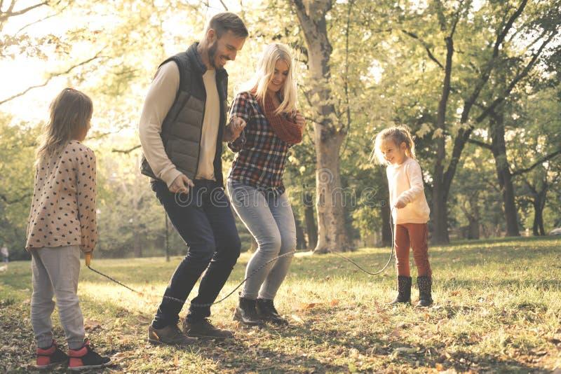 跳横跨跳绳小女孩的父母拿着绳索  库存照片